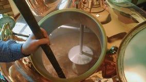 一个人倒麦芽入酿造啤酒的桶 煮沸黑啤酒液体 股票录像