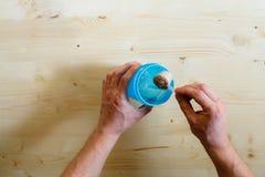 一个人倾吐乳清蛋白震动对蓝色 乳清蛋白,一种健康生活方式,人倾倒在小圆面包之上的乳清粉末 并且瓢干式混合 库存照片