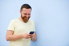 一个人做在滑稽的面孔,并且幽默电话做严肃的面孔,广告公司 免版税库存图片