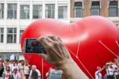 一个人做照片大红色心脏在街道 免版税库存图片