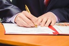 一个人写一支笔 仅一个人手和文件 免版税库存图片