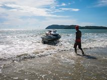一个人准备好对驾驶在海滩的快艇 库存照片