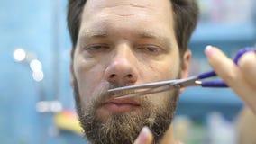 一个人切开他的有剪刀的髭 股票视频