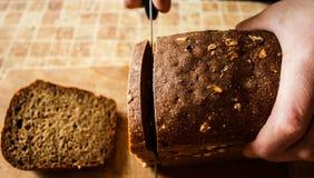 一个人切玉米面面包 库存图片