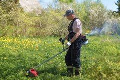 一个人割在割草机的草 总之和工具 免版税库存图片