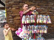 一个人卖玩具和泡影制造商在边路 免版税库存照片
