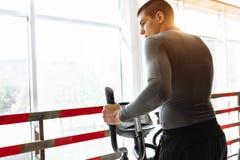 一个人参与在体育自行车的训练在健身房,早晨训练 库存照片
