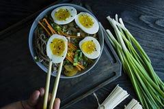 一个人吃荞麦soba在汤的面条用调味汁和小菜 E r 黑木背景 ?? 库存图片