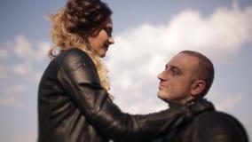 一个人和一个女孩皮夹克的坐一个红色摩托车亲吻 约会在城市公园的背景 股票录像