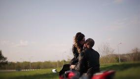一个人和一个女孩皮夹克的坐一个红色摩托车亲吻 约会在城市公园的背景 股票视频