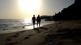 一个人和妇女步行沿海滩,握手 股票视频