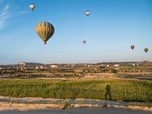 一个人和热空气气球的树荫在背景在卡帕多细亚,土耳其 免版税库存照片