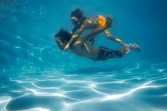 一个人和男孩的水下的图象 免版税库存照片