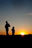 一个人和他的儿子的剪影有日落背景 夏令时 库存照片