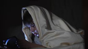 一个人哄骗使用片剂个人计算机在毯子下在晚上 男孩打计算机游戏 股票录像