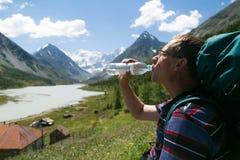 一个人喝从一个瓶的水在山的背景中 免版税库存照片