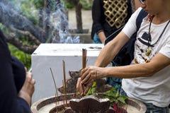 一个人在一个特别碗投入灼烧的香火棍子 图库摄影
