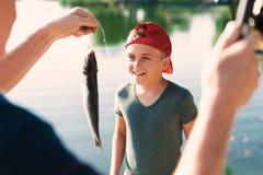 一个人在一个红色盖帽显示男孩他风行他转动的一条鱼 图库摄影
