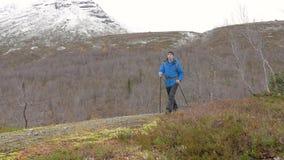 一个人在一个美丽的公园单独旅行 特写镜头 他攀登小山 使用一个背包和用特别棍子为 影视素材