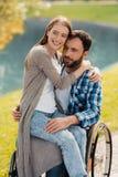 一个人在一个轮椅坐在一个美丽的绿色公园 妇女坐他的膝部并且拥抱他 免版税库存图片