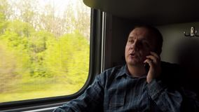 一个人在一列移动的火车的窗口附近由电话情感地沟通 股票录像