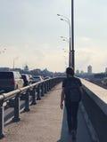 一个人在一座桥梁走在城市 免版税库存图片