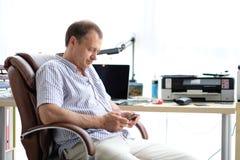 一个人在一把扶手椅子坐在他的办公室 库存图片