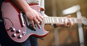 一个人在一把红色电吉他使用 免版税库存照片