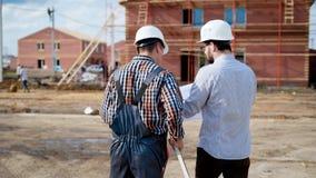 一个人在一致的一位建造者和一件防护盔甲的一位成人建筑师在他们的手上举行的一个计划 股票视频