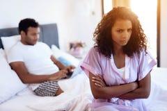 一个人在与一台膝上型计算机的床上说谎在他的膝部 在他前是他的性感的女用贴身内衣裤的女孩 人忽略她 免版税库存图片