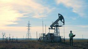 一个人在与井架的一个领域走 油萃取产业概念 股票录像