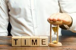 一个人在与字时间的木块附近投入滴漏 时间管理和适当的发行的概念 计划的事务 免版税库存图片