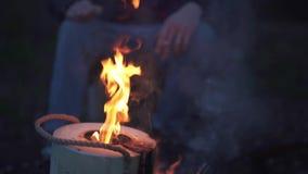 一个人在与cigaret的篝火附近在手中坐 抽烟由火的林务员在森林里 影视素材