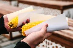 一个人在从一位卖主买的他的手可口煮沸的玉米举行在Sultanahmet广场在伊斯坦布尔,土耳其 库存照片