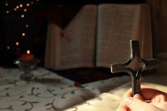 一个人在他的手上拿着一个十字架并且祈祷 库存图片