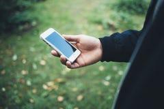 一个人在他的手上拿着一个手机 免版税库存图片