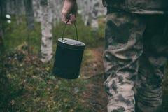 一个人在他的手上运载铁罐烹调的在它的食物 免版税库存照片