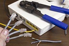 一个人在他的手,一个调制解调器上拿着一网络缆绳在书桌,特写镜头,路由器上 免版税库存图片