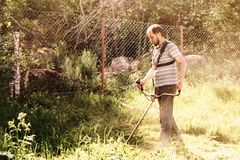 一个人在他的有整理者的庭院里割草 库存图片