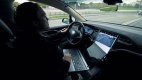 一个人在他的汽车慢慢地驾驶,当操作膝上型计算机时 股票录像