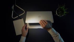 一个人在光在他的玻璃转动投入并且开始工作,当坐在桌上使用一台膝上型计算机在晚上时 股票录像