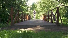 一个人在公园骑横跨桥梁的一辆自行车 慢的行动 股票视频