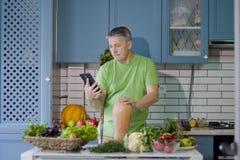 一个人在厨房准备蔬菜菜肴 查寻在片剂显示的一份食谱 免版税库存照片