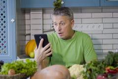 一个人在厨房准备蔬菜菜肴 查寻在片剂显示的一份食谱 库存照片