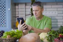 一个人在厨房准备蔬菜菜肴 查寻在片剂显示的一份食谱 免版税库存图片