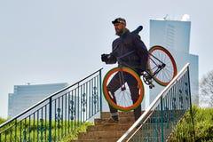 一个人在台阶拿着一辆自行车并且站立以高层建筑物为背景 晴朗的日 库存照片