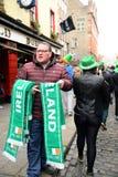 一个人在圣帕特里克` s天ParadeÂ卖了围巾在都伯林,爱尔兰, 2015年3月18日 库存照片