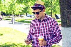 一个人在城市站立,用咖啡或茶,在电话的社会网络写入一则消息,在夏天 免版税库存图片