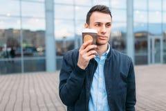 一个人在城市附近走,并且从一纸杯的饮用的咖啡,一个英俊的人走动和休息, backgrou的人 免版税图库摄影