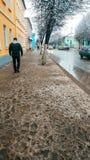 一个人在城市,走沿有肮脏的雪的路沿与水坑的路旁,在黄色前面 图库摄影